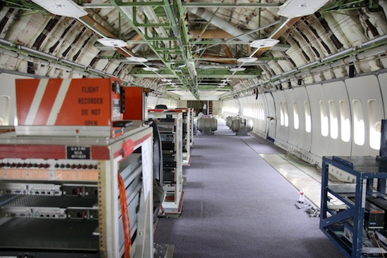 Looking aft in the main cabin of the Boeing 747 prototype, with racks of flight test equipment in the foreground and water ballast barrels in the background. Ted Huetter/The Museum of Flight.