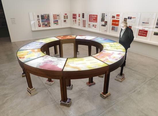 Muntadas, On Translation: La mesa de negociación II, 2005. Wooden table, silkscreened Plexiglas, light and books. Courtesy of the artist and Galeria Joan Prats. Photo: Rachel Topham, Vancouver Art Gallery. © Muntadas/SODRAC (2013).