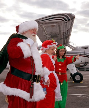 An Elf directs Santa and Mrs. Claus after their airplane landing at The Museum of Flight. Ted Huetter/The Museum of Flight, Seattle.