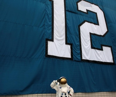 "The Museum of Flight astronaut strikes a pose in front of the Museum's Seahawks ""12th MAN"" flag next to the Museum's main entrance. Janessa Rosick/The Museum of Flight."