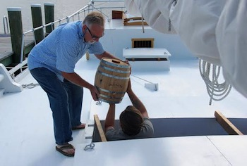 Olivins Owner and Operator Bill Acosta, left, hands over a wooden barrel of balsamic vinegar to CBMM Boat Yard Manager Michael Gorman, right, aboard the skipjack Rosie Parks.