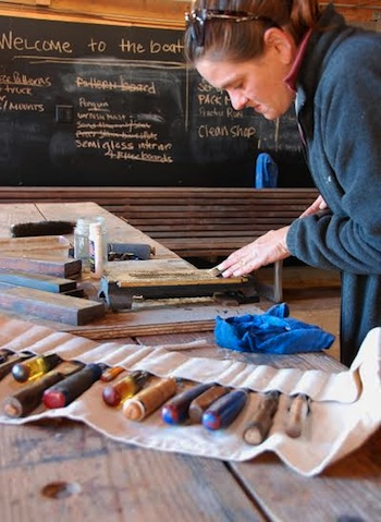 CBMM Boatyard Program Manager Jenn Kuhn uses a whetstone to hone a chisel in the museum's boatshop.
