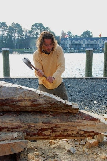 CBMM Shipwright Apprentice James DelAguila uses a broad ax to shape one of the logs for a new three-log sailing canoe at the Chesapeake Bay Maritime Museum.