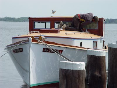 A Chesapeake Bay Maritime Museum apprentice works on the brightwork of the 1926 trunk cabin power cruiser Isabel along the Miles River in St. Michaels, Md.