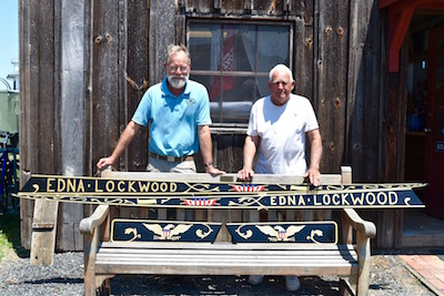 CBMM Assistant Curator of Watercraft Richard Scofield, left, stands with CBMM volunteer and carver Winslow Womack, right, who recently used a relief carving technique to craft these new name boards for the 1889 log-bottom Edna E. Lockwood, currently under restoration at CBMM through 2018.