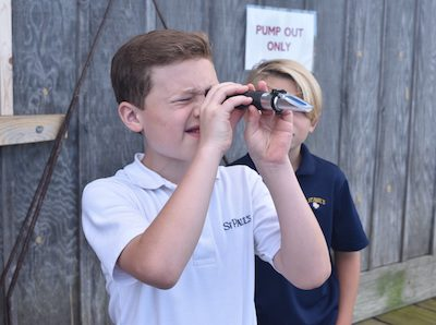 St. Paul's students use a refractometer to measure the salinity of the Miles River. Oysters prefer to live in salty water, so this measure helps students assess the suitability of the surrounding environment.